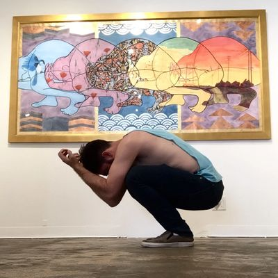 The artist, K Ryan Henisey, kneels before his painting, mimicking the pose of the figure in the art.