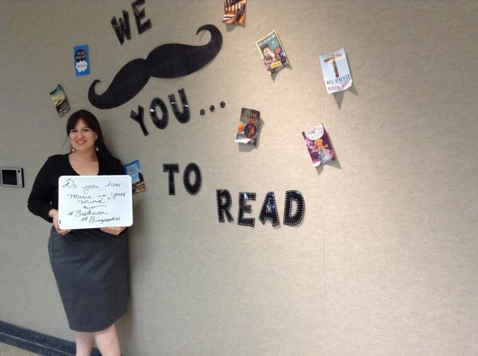 Ashley standing in front of a sign that says we mustache you to read.