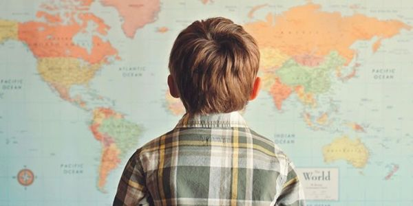 a boy facing a large map of the world, with his back to the camera