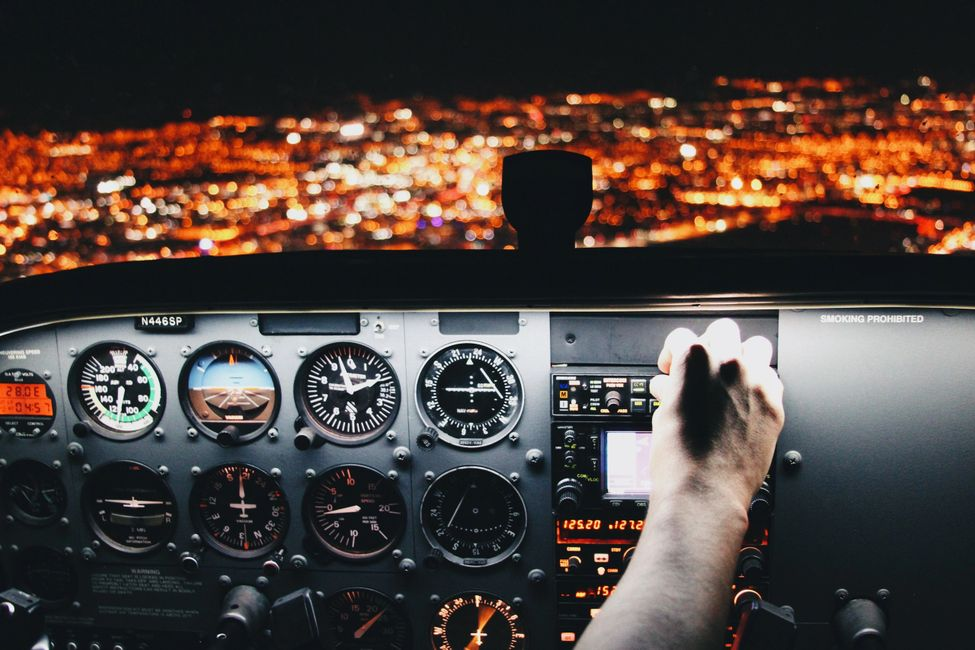Cessna Cockpit at night with pilot pressing knobs.