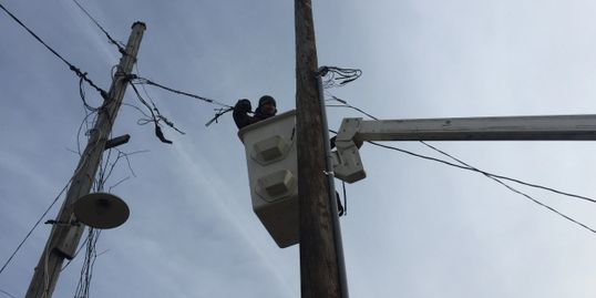Hardon's using a bucket truck to move electrical service from an old pole to a new pole.
