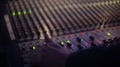 Hand on audio mixing console