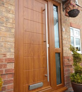 Golden Oak Solid Core front door with mid rail side panel and long bar handle fitted in Linby.