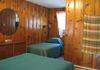 Group cabin has two bedrooms each with a bathroom with shower, double bed and single bed.