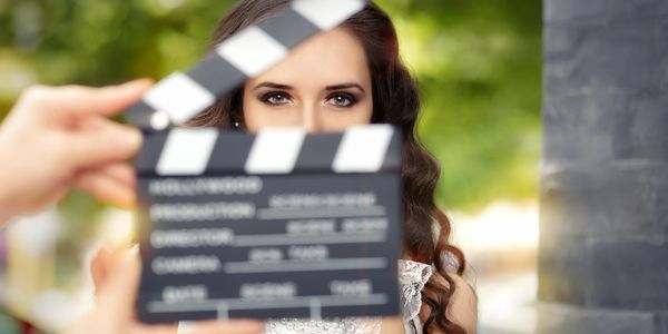 An actress with beautiful eyes just before slate depicting scene and take number is closed.