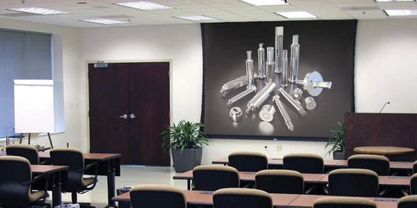 Image of a conference room with chairs facing towards a projector display on the wall.