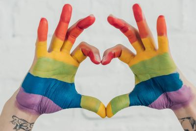 Rainbow painted  hands forming a heart.