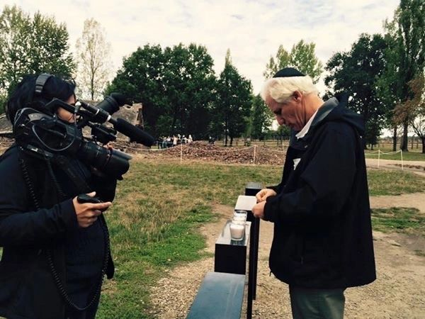 Cinematograper Nausheen Dadabhoy captures Fred lighting a memorial candle at Auschwitz