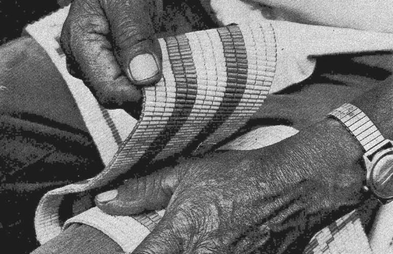 The late Chief Jake Thomas' hands with a Wampum belt.