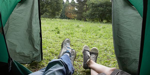 A couple looking past their tent feet at a meadow through an open tent door.