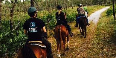 Guided horseback trail rides at Lake Louisa. Friends horse back riding on a forest trail.