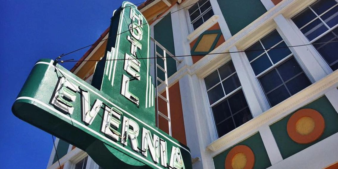 a lower angled photo of the Hotel Evernia front sign, which is composed of neon lighting on green