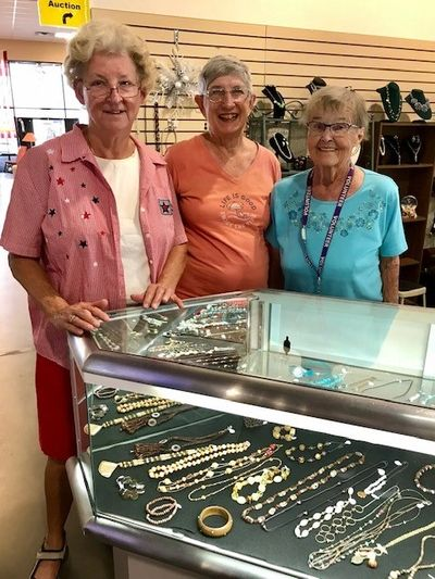 Volunteers standing at the jewelry counter.