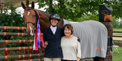 Brawley Farms owner and horse trainers receive championship ribbon at horse show.
