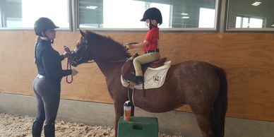 Young rider on pony receiving instruction from riding instructor.