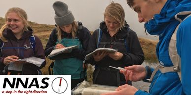 A group of walkers practicing navigation with maps and compass on a NNAS bronze award course