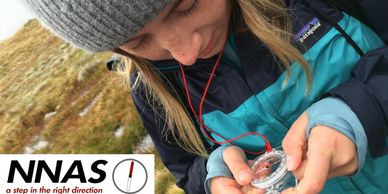 A female walker practicing navigation with maps and compass on a NNAS silver award course