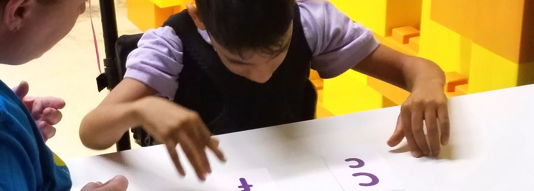 close up photo of student at desk looking at alphabet flashcards