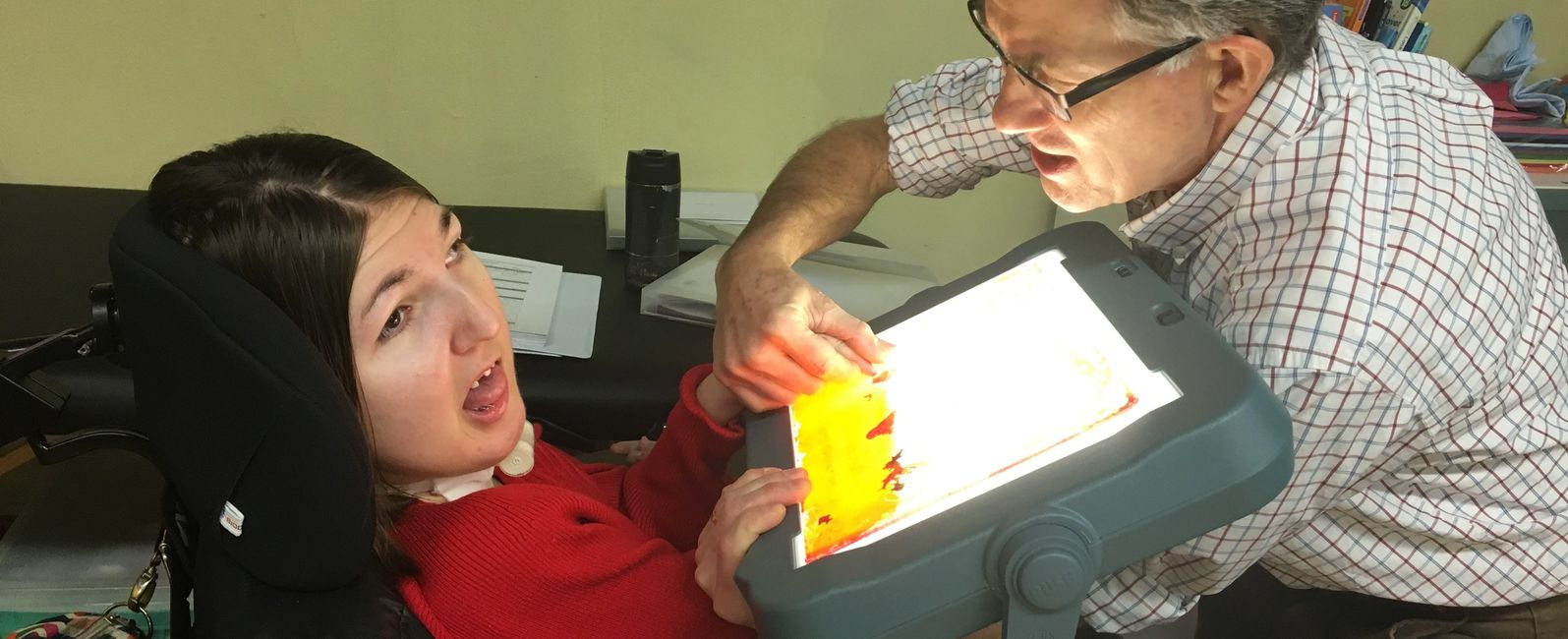 photo of vision specialist assisting  student to touch a device with a lit screen