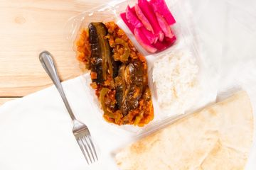 eggplant with tomato garlic and onions and a side of rice, turnip pickles, and pita bread