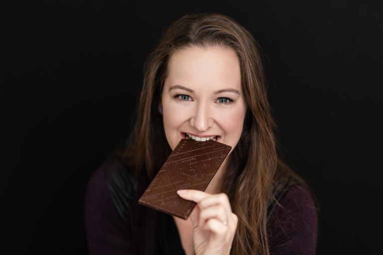 Jessica eating taking a bite of a craft chocolate bar Ritual