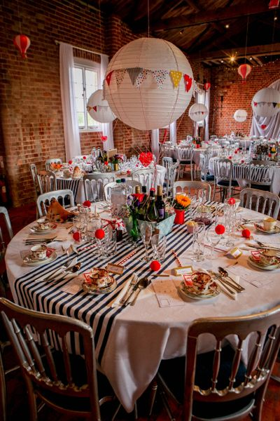 Stripe centre pieces and paper lantern hot air balloons adds drama and fun to a circus themed wedding at Barton Manor in Whippingham, Isle of Wight. Red noses act as favours and palm reading fish for an added spot of fun.
