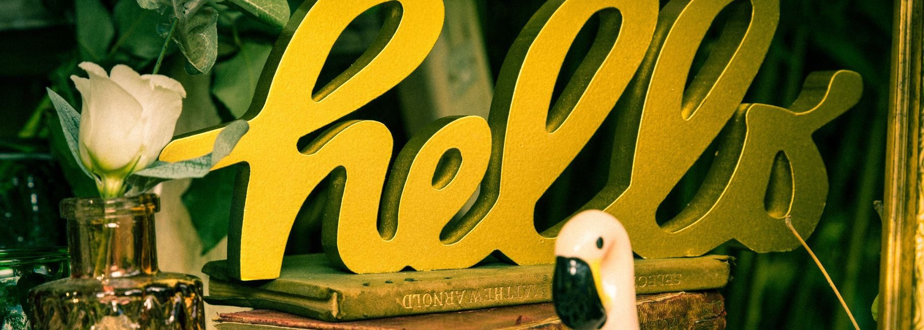 Gold italic wooden hello sign, vintage books, a small pink glass vase and pink flamingo resting on