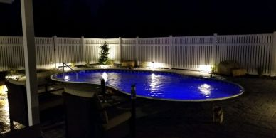 Swimming pool landscape lighting and paver patio surround with privacy fence and accent plantings by LANDDescapes, LLC Landscape Design Contractor