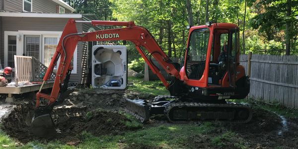 Excavator digging a 24' dia hole for a pool install excavating contractor, Atkinson NH