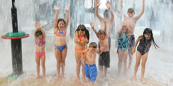 Kids standing under tipping bucket in the waterpark