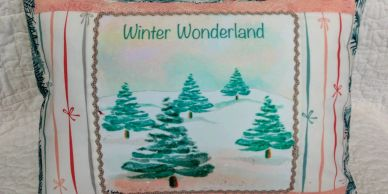 Pillow made from winter wonderland fabric art print featuring conifer trees and snow