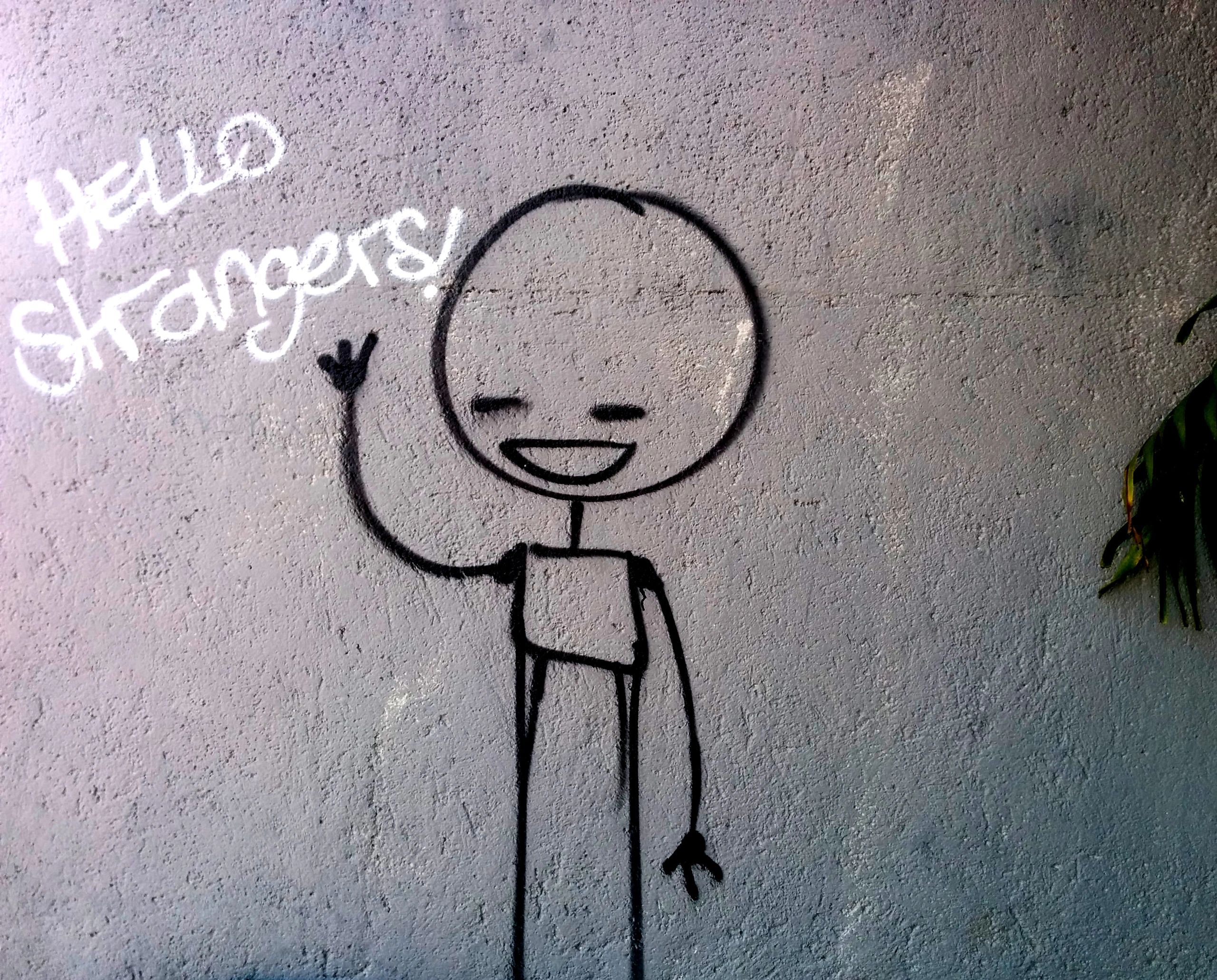 Graffiti of stick man waving and text saying 'Hello strangers!'