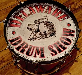 aBass Drum on a wooden floor with a Delaware Drum Show Logo front head of a vintage drum set.