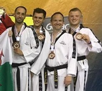 Chris (second from left) collects his medal at the Taekwondo World Championships in July 2018