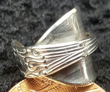 Tiny antique sterling silver mustard spoon repurposed into a ring to celebrate the birth of a child (ring is next to a 1p piece for size comparision