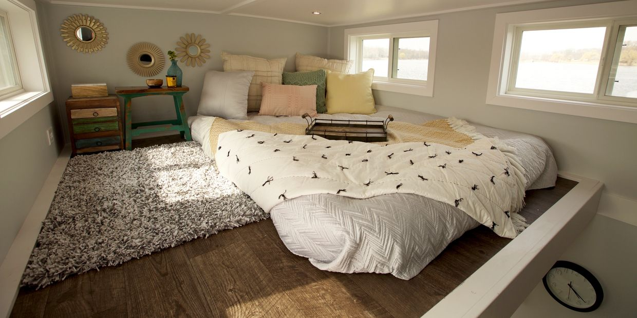 Bedroom loft interior white walls gray bed spread dark wood floors modern wood trim work