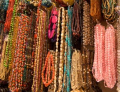Huge wall of natural handmade beaded necklaces. Learn about gem treatments and jewelry care here.
