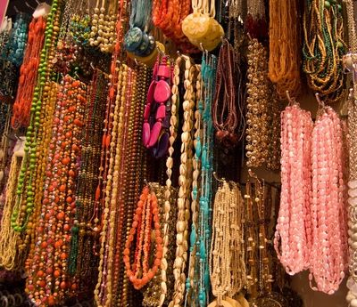 Huge wall of handmade artisan gemstone necklaces. Learn how to care for your J'tara jewelry here.
