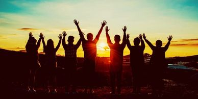 Seven people standing on the edge of a mountain at sunset, hands outstretched above their heads