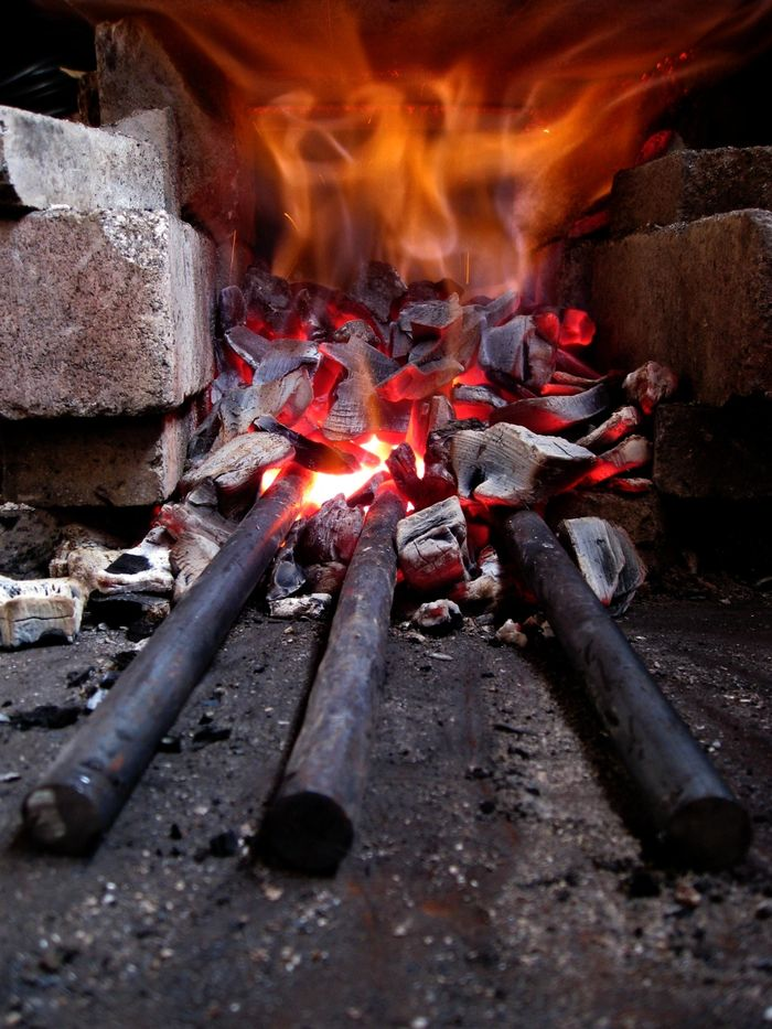 There are three pieces of steel heating up in a charcoal forge.