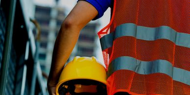 Construction worker carrying hard hat.