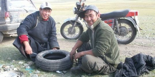 Two Mongolian men fixing our Micra's puncture