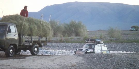 Classic Austin Mini crossing a river in Mongolia