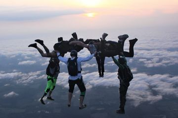 Experienced skydivers make a hybrid formation at sunset at Skydive Panama City.