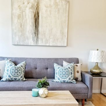 grey sofa with gold lamp, large scale artwork and wooden coffee table for home staging