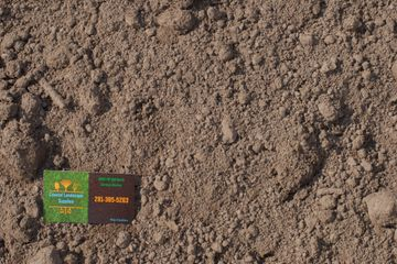 Top soil with Coastal Landscape Supplies business card in the corner.