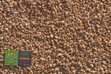 Pea Gravel with Coastal Landscape Supplies business card in the corner.