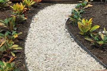White limestone gravel path with plants and mulch surrounding it.