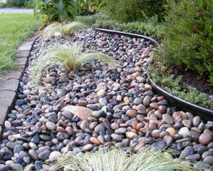 Garden bed of beach pebbles with aztec grass.
