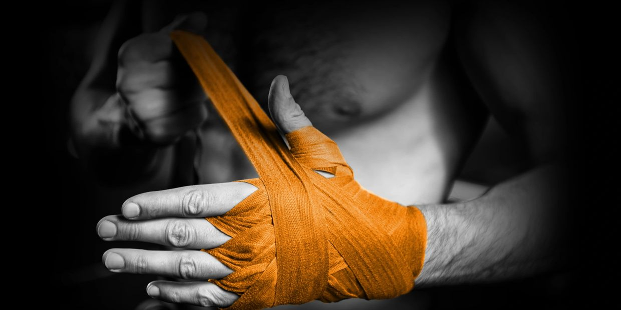 man wrapping hands with wrist wraps for boxing